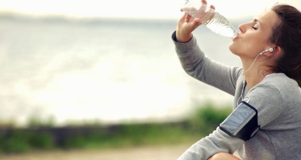 woman drinking water after excercise